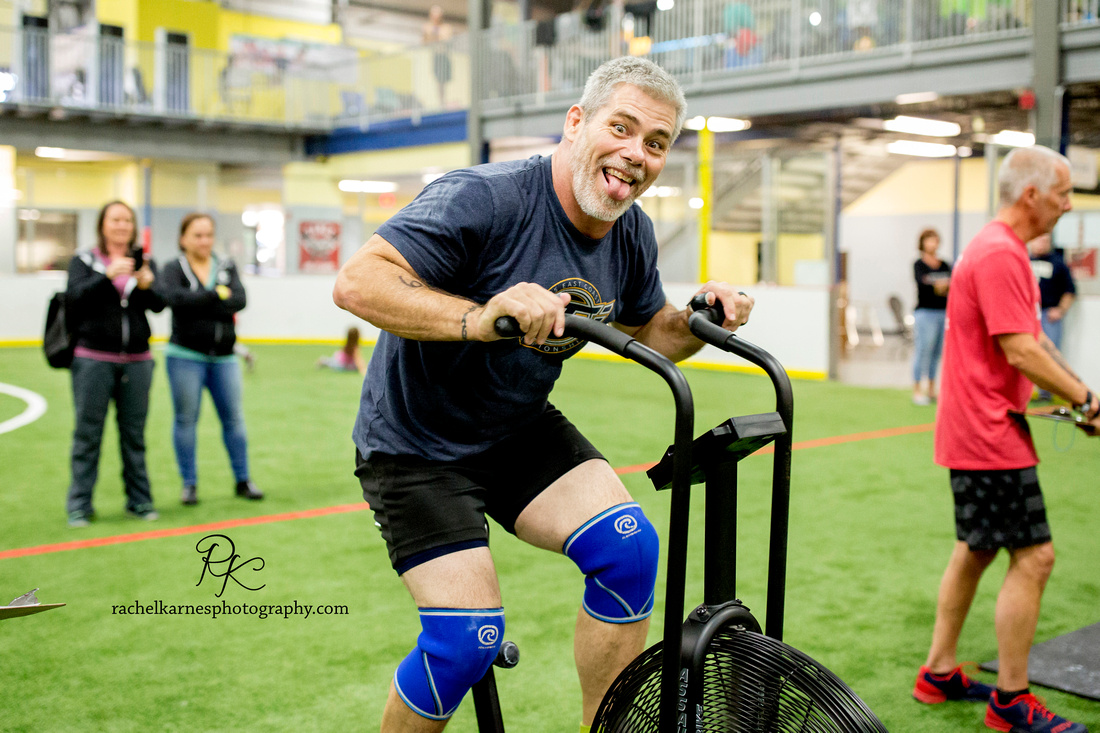 male-athlete-smiling-on-air-assault-bike