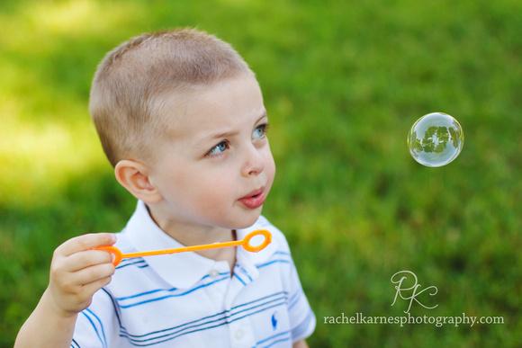 Little boy blowing bubbles in VA park