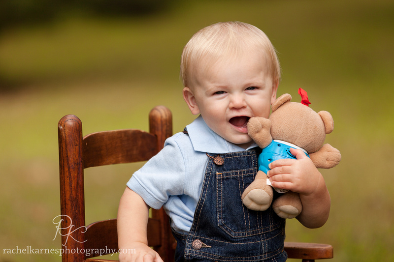 toddler in overalls with teddy bear in rocking chair outside